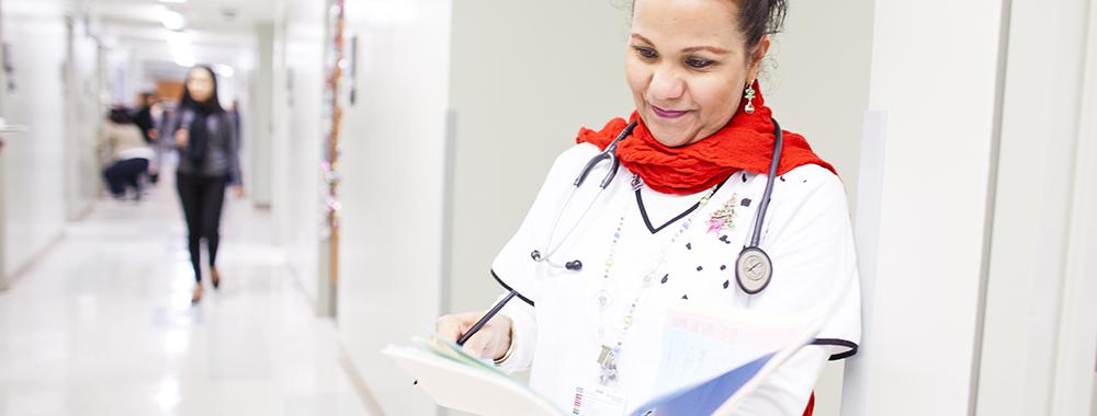 female doctor holding a folder of information she is reading in a hospital corridor