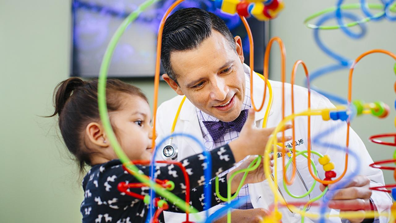 UC Davis Health doctor and child playing a dexterity game.