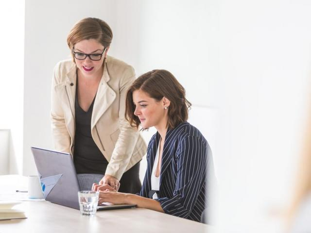one woman helping other woman on computer