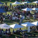 Aerial view of vendor pop-up tents on Hutchison Field at UC Davis, with people visiting each tent.
