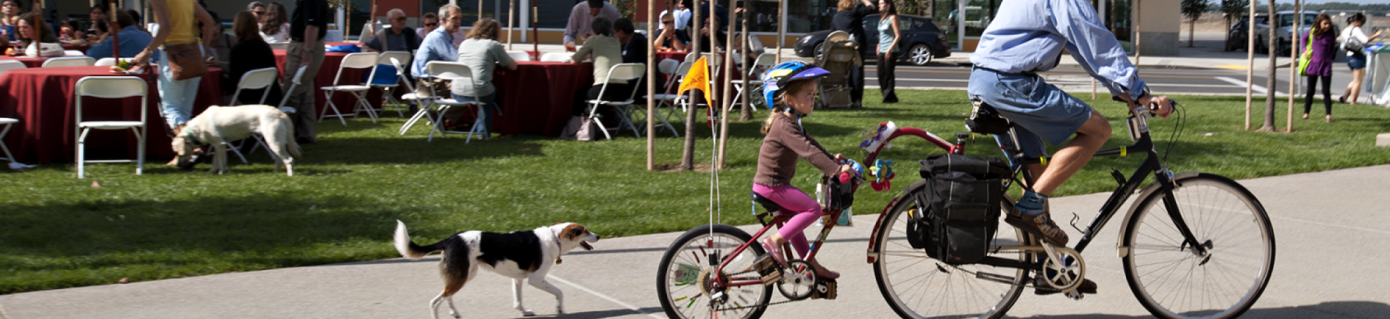 men and his daughter riding bikes with their dog running behind
